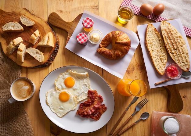 Desayuno continental croissant huevos tocino pan