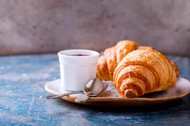 Desayuno continental con cruasanes recién hechos. delicioso horneado con mermelada de bayas