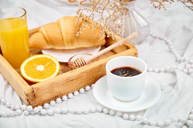 Desayuno continental en sábanas blancas.