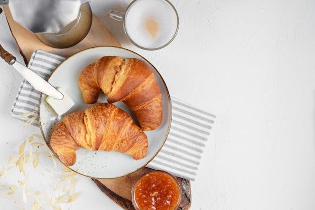 Desayuno continental, una taza de café con leche, dos cruasanes, mantequilla y mermelada de naranja en una tabla de madera, vista superior