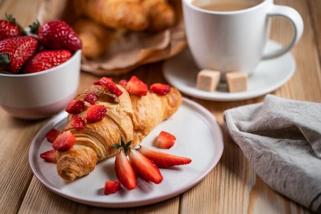 Desayuno continental con variedad de pasteles, cafés y fresas frescas.