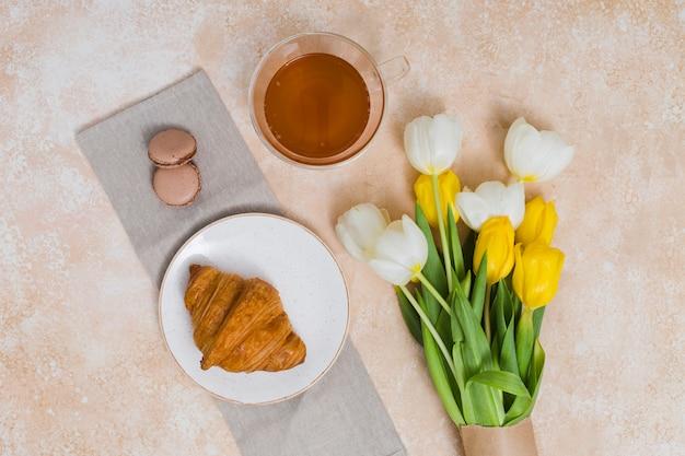 Desayuno con croissant y flores