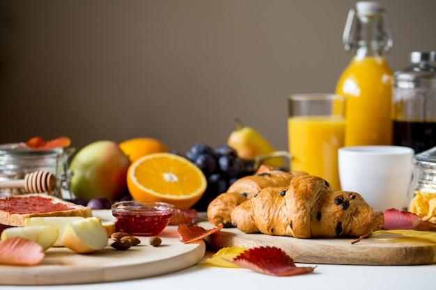 Desayuno con croissant. jugo de naranja en una botella de vidrio.