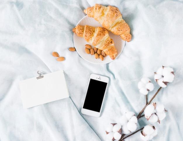 Desayuno con croissant y un móvil
