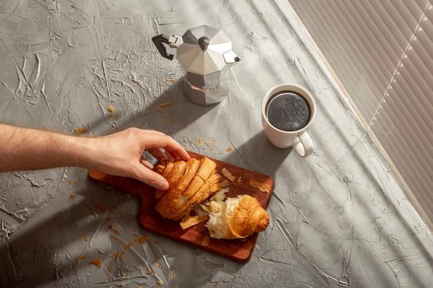 Desayuno con croissant en tabla de cortar y café negro. concepto de desayuno y comida de la mañana.