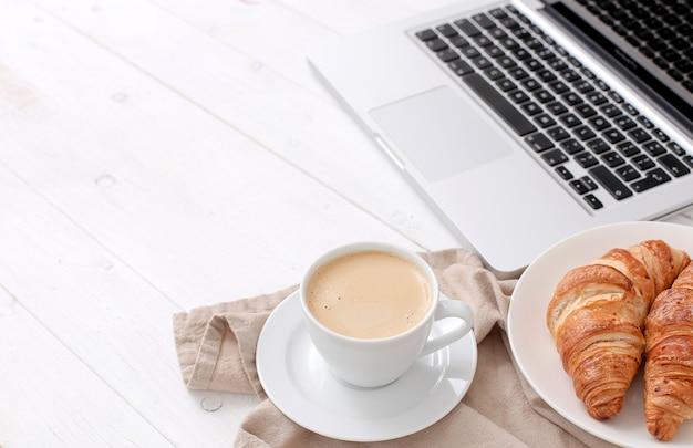 Desayuno con croissants y café cerca de una computadora portátil.