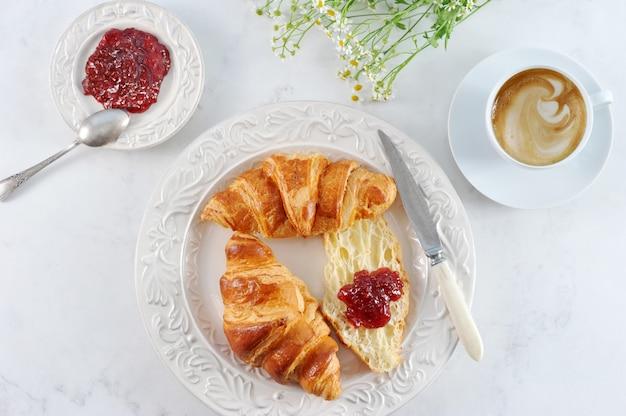 Desayuno con croissants, mermelada de frambuesa y café.