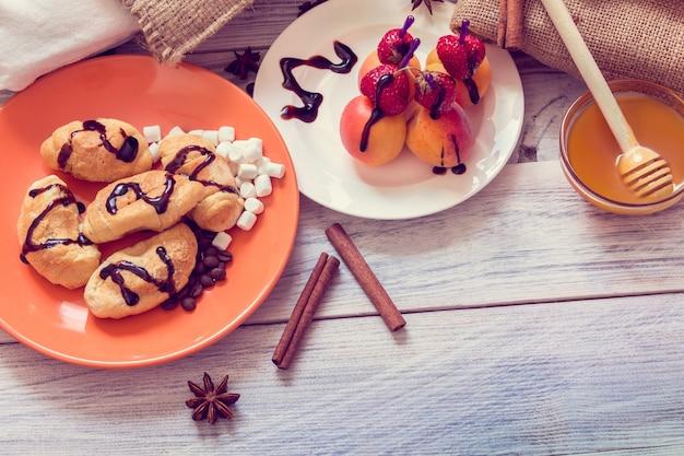 Desayuno con croissants, miel y canapés de fresas y albaricoques.