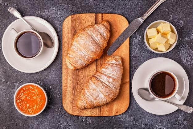 Desayuno con croissants recién hechos, jugo de naranja y café.