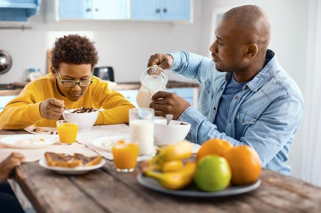 Desayuno delicioso. encantador joven vertiendo un vaso de leche mientras su hijo mayor sentado junto a él y comiendo cereales