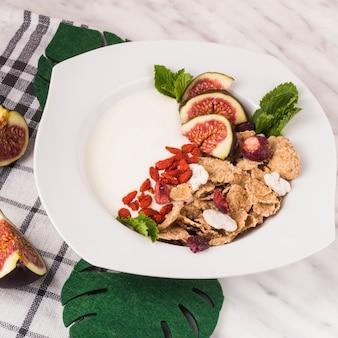Desayuno delicioso; hojas de monstera falsas y rebanadas de higo con servilleta de cocina sobre una superficie de mármol blanco