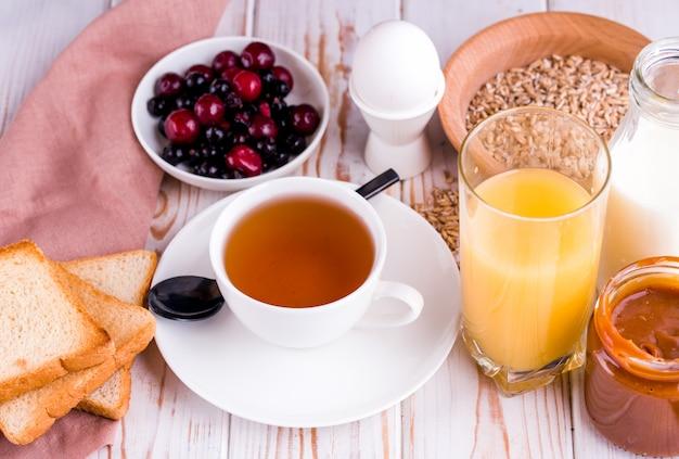Desayuno delicioso, saludable y abundante sobre la mesa blanca. huevos, avena, leche, té, tostadas de plátano, caramelo salado casero, panqueques con fruta, jugo de naranja. parte superior