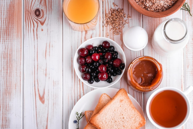 Desayuno delicioso, saludable y abundante sobre la mesa blanca. huevos, avena, leche, té, tostadas de plátano, caramelo salado casero, panqueques con fruta, jugo de naranja.