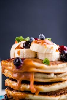 Desayuno delicioso, saludable y abundante sobre la mesa blanca. panqueques con fruta, jugo de naranja. parte superior