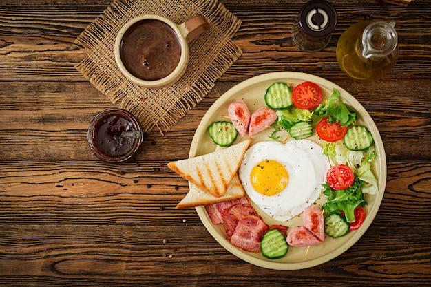 Desayuno en el día de san valentín: huevo frito en forma de corazón, tostadas, salchichas, tocino y verduras frescas. desayuno inglés. taza de cafe. vista superior