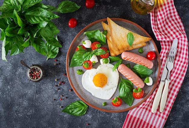 Desayuno en el día de san valentín: huevos fritos en forma de corazón, salchichas, tostadas y ensalada caprese.