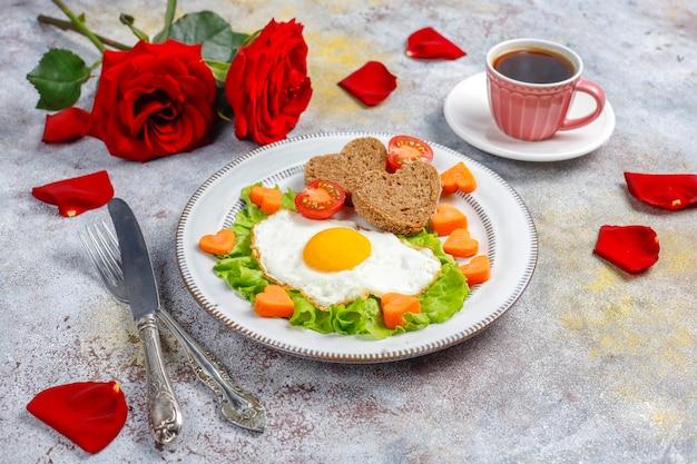 Desayuno el día de san valentín: huevos fritos y pan en forma de corazón y verduras frescas.