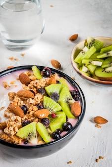 Desayuno de dieta saludable: tazón de batidos, con yogur, arándanos frescos, kiwi, avena granola, nueces almendras