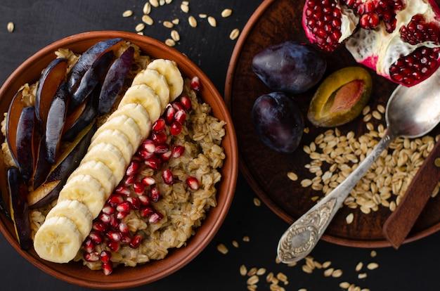 Desayuno dietético de un tazón con gachas de avena, plátano, semillas de granada y ciruela