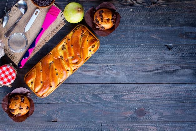 Desayuno con diferentes pasteles y frutas en madera