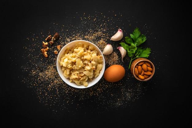 Desayuno con ensalada de coliflor asada con nueces variadas en un tazón y verduras y huevos