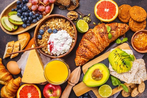 Desayuno equilibrado saludable sobre un fondo oscuro. muesli, leche, zumo, croissants, queso, galletas.