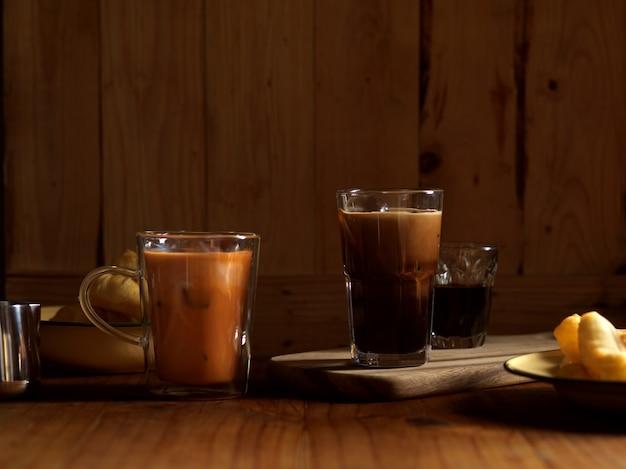 Desayuno de estilo tailandés con café helado tae de leche tailandesa y palito de masa frita sobre mesa de madera