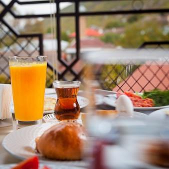 Desayuno en el exterior con vista lateral de zumo de naranja y té