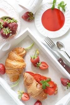Desayuno francés con croissant y mermelada de fresa sobre fondo blanco.