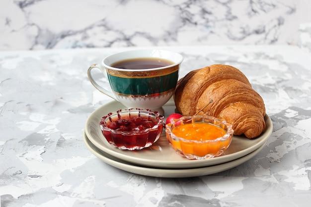 Desayuno francés con cruasanes, mermelada de albaricoque, mermelada de cereza y una taza de té, flores rojas y amarillas.
