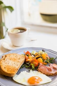 Desayuno fresco saludable con taza de té en mesa blanca