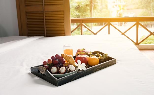 Desayuno fruta croissants jugo de naranja en una bandeja de madera negra sobre sábana blanca comida sana