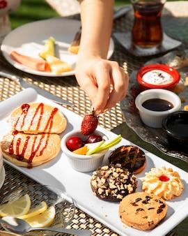 Desayuno con fruta y galletas variadas.