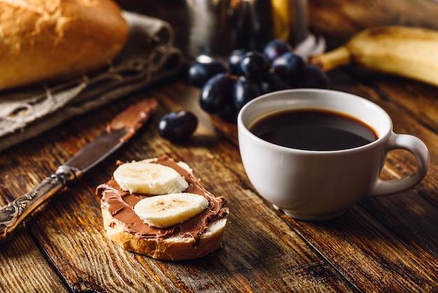 Desayuno con fruta, sándwich y café.