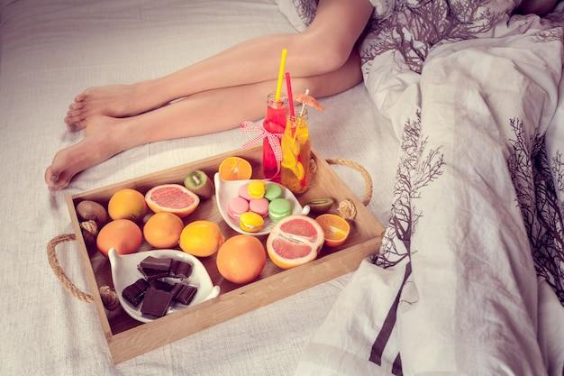Desayuno de frutas a cama y piernas femeninas.