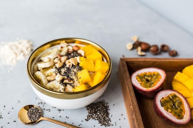 Desayuno gachas de avena con frutas frescas, semillas de chía y avellanas.