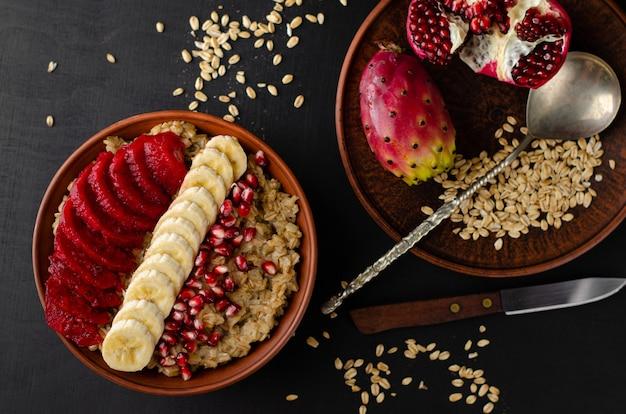 Desayuno con gachas de avena, plátano, semillas de granada y fruta de cactus opuntia.