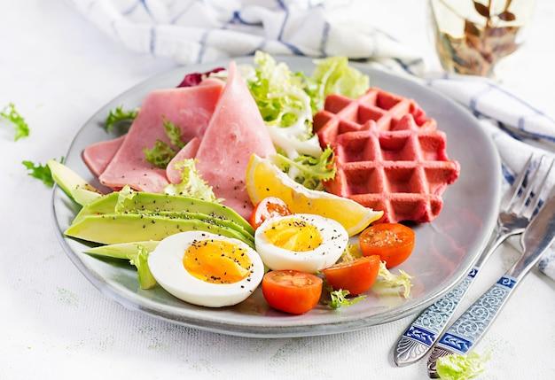 Desayuno con gofres de remolacha, huevo cocido, jamón, tomate y rebanada de aguacate sobre superficie blanca