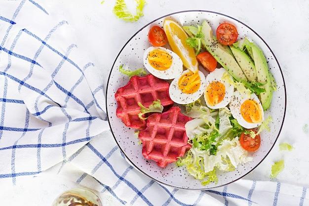 Desayuno con gofres de remolacha, huevo cocido, tomate y rodajas de aguacate sobre superficie blanca