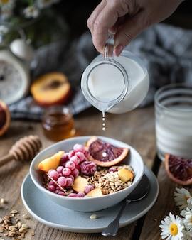 Desayuno de granola con frutas y bayas y miel y un vaso de leche o yogurt en una mesa de madera. ramo de margaritas. rústico