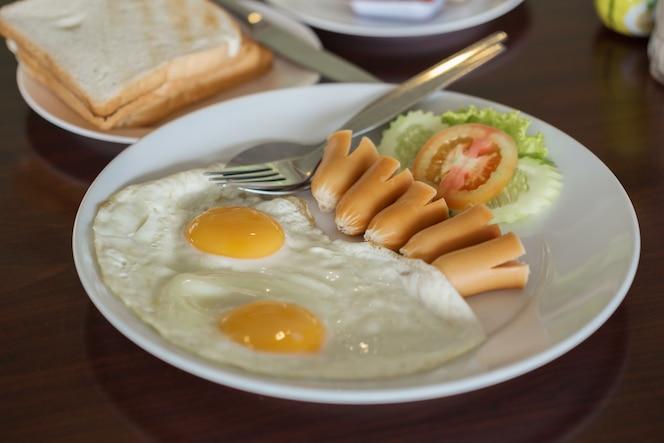 Desayuno (huevo frito, perro caliente y pan)