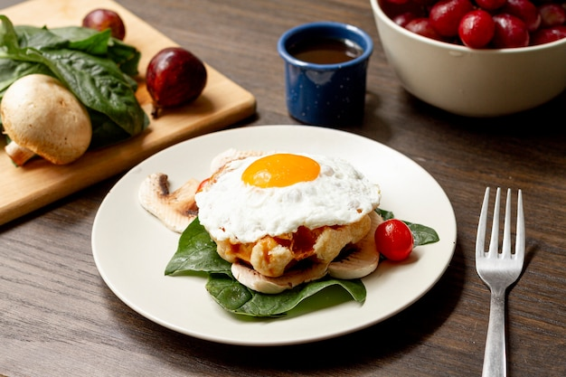 Desayuno de huevo frito con tomate y café.