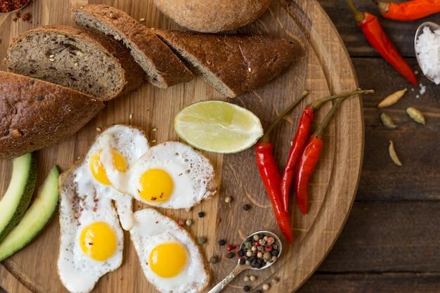 Desayuno de huevos fritos, pan, aguacate y diversas especias en una tabla de madera.