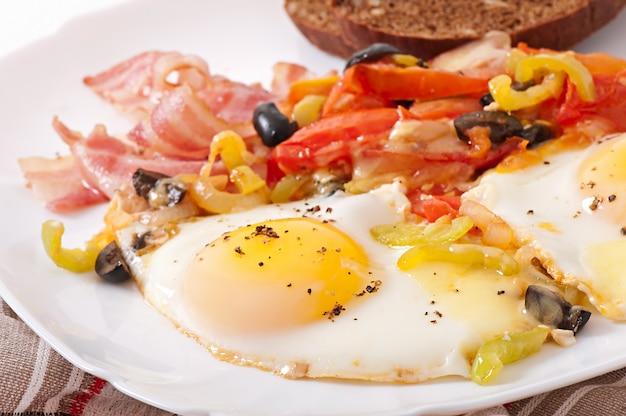 Desayuno: huevos fritos con tocino, tomates, aceitunas y lonchas de queso.