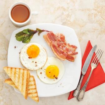 Desayuno con huevos fritos, tostadas, tocino y té sobre superficie de mármol.