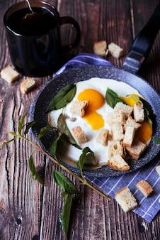 Desayuno de huevos y pan rallado en mesa de madera.