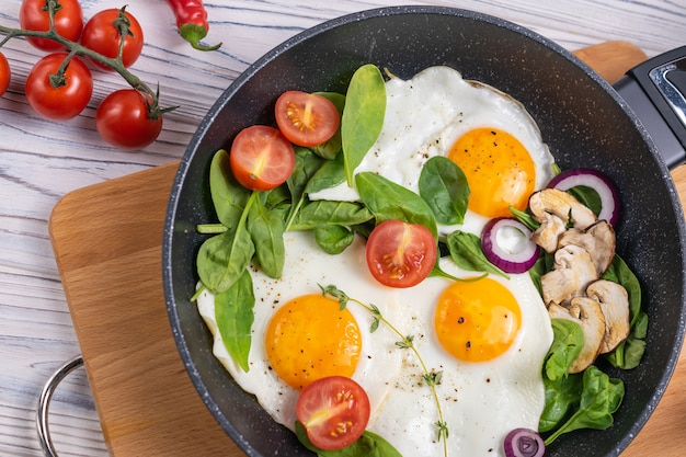 Desayuno con huevos, tomates con champiñones y hojas frescas de espinaca.