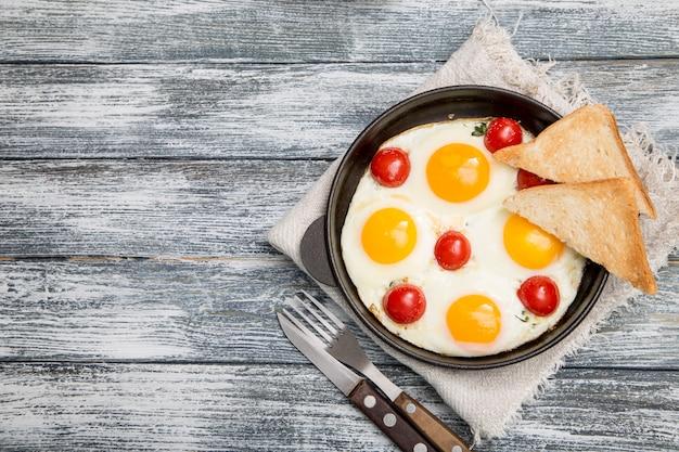 Desayuno con huevos, tomates cherry, tocino y tostadas recién tostadas.
