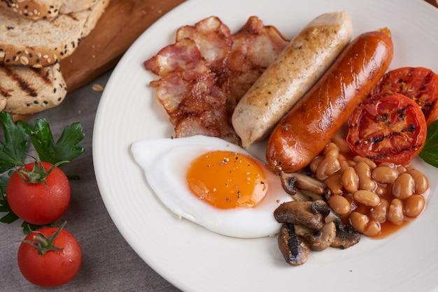 Desayuno inglés completo tradicional con huevos fritos, salchichas, frijoles, champiñones, tomates asados y tocino en un plato, tostadas, mantequilla, mermelada en una tabla de madera