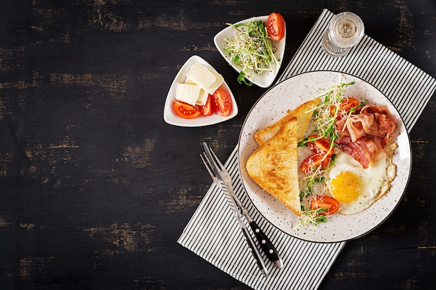 Desayuno inglés: ensalada de tostadas, huevo, tocino, tomates y microgreens. vista superior. lay flat